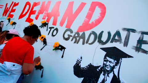 """A woman visits a mural at the """"End of School Year Peace March and Rally"""" Friday at St. Sabina Church in Chicago."""