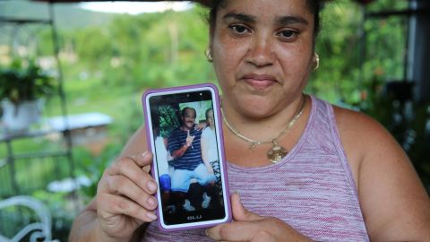 """Lisa De Jesús holds a picture of her deceased friend, """"Rey Bruquena,"""" or """"Rey Crab,"""" who earned that nickname because of his love for the ocean."""