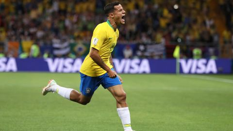 Philippe Coutinho wheels away after curling home Brazil's opener.