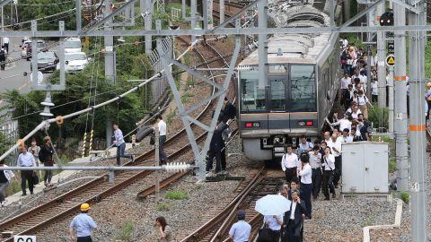 Passengers walk along railroad tracks after the earthquake.