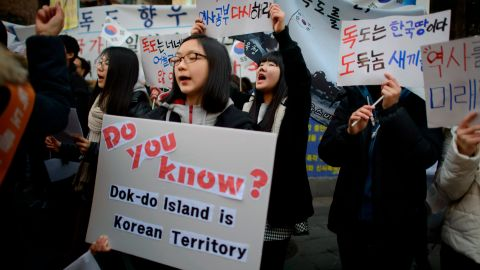 Demonstrators hold placards and shout slogans during a protest over the disputed Dokdo/Takeshima islands in front of the Japanese Embassy in Seoul on February 22, 2014.