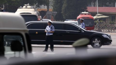 The motorcade in which Kim is believed to be traveling passes by policemen as it leaves the Beijing Capital International Airport.