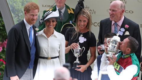 Prince Harry and Meghan present a trophy to jockey Frankie Dettori for his winning ride on Without Parole as trainer John Gosden (right) watches on.