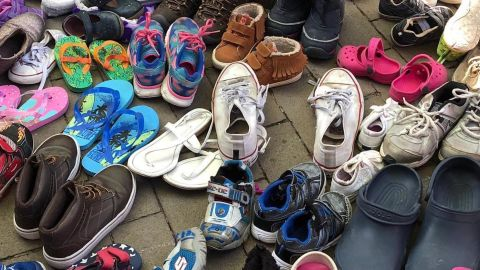 Children's shoes crowd the sidewalk at the Philadelphia immigration protest.