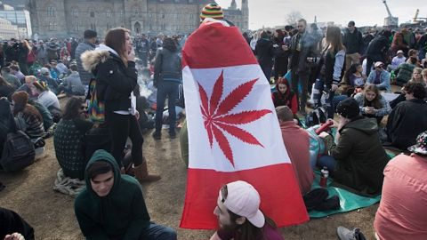 A man wears a Canadian maple leaf flag with marijuana leaf during the annual 4/20 rally on Parliament Hill in Ottawa in 2018.