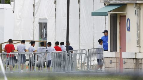 Immigrant children walk in a line outside the Homestead Temporary Shelter for Unaccompanied Children, a former Job Corps site that now houses them, on Wednesday, June 20, 2018, in Homestead, Fla. (AP Photo/Brynn Anderson)
