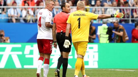 Denmark's Simon Kjaer and Kasper Schmeichel confront referee Antonio Mateu after the penalty award.