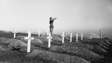 """On December 13, 1950 during memorial services at the First Marine cemetery in Hungnam, Korea, Corporal Charles Price sounds """"Taps"""" over the graves of fallen U.S. Marines following the division's heroic break-out from Chosin Reservoir. (Photo by © CORBIS/Corbis via Getty Images)"""