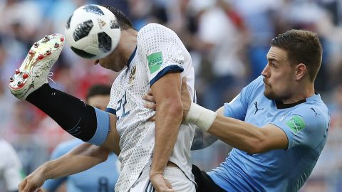 Russia's Artem Dzyuba, in white, competes with Uruguay's Sebastian Coates during Uruguay's 3-0 victory on June 25. Uruguay won all three of its matches in the group stage. This was Russia's first loss.