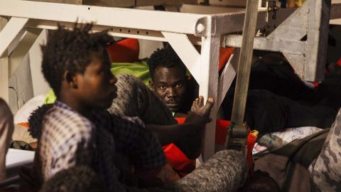 Rescued migrants sit in the search and rescue ship Lifeline as the boat remained stranded Monday.