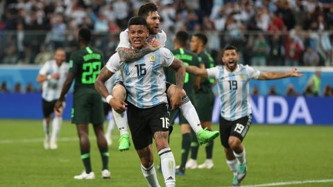 Argentina star Lionel Messi rides on the back of Marcos Rojo after Rojo's late winner against Nigeria on June 26. With the 2-1 victory, Argentina clinched a spot in the next round of the tournament.
