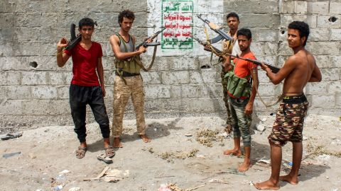 """Yemeni fighters from the Amalqa (""""Giants"""") Brigades loyal to the Saudi-backed government stand pointing their Kalashnikov assault rifles towards a Huthi-rebel banner painted on a wall, reading in Arabic """"God is the greatest... Death to America, death to Israel, cursed be the Jews, victory for Islam"""", on the southern outskirts of the Red Sea port city of Hodeida near the airport on June 21, 2018. - The """"Giant Brigades"""" are a former elite unit of the Yemeni army rebuilt by the UAE which has been at the vanguard of the offensive, reinforced by thousands of fighters from southern Yemen. (Photo by Saleh Al-OBEIDI / AFP)        (Photo credit should read SALEH AL-OBEIDI/AFP/Getty Images)"""