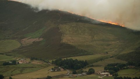 A large moorland wildfire burns on the hills above Dove Stone Reservoir near Stalybridge, northwest England.