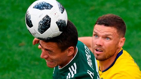 Mexican defender Hector Moreno heads the ball in front of Swedish forward Marcus Berg.