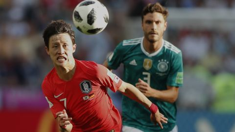 South Korea'sLeeJae-sung, left, chases down a ball with Germany's Jonas Hector.