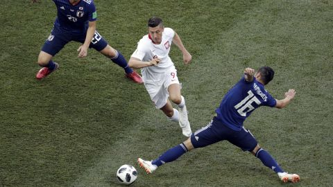 Poland forward Robert Lewandowski dribbles through two Japan players.