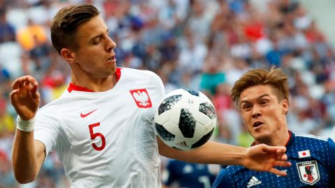 Poland's Jan Bednarek, left, competes for the ball with Japan's Gotoku Sakai on June 28. Poland won 1-0, but Japan advanced to the next round.