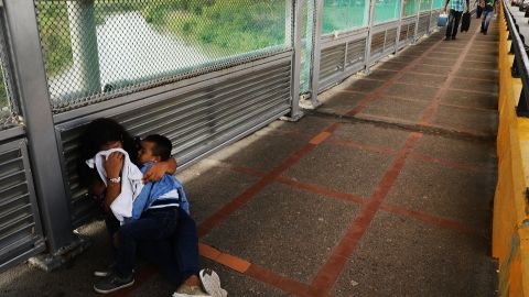 BROWNSVILLE, TX - JUNE 22:  A crying  Honduran woman and her child wait along the border bridge after being denied into the Texas city of Brownsville which has become dependent on the daily crossing into and out of Mexico on June 22, 2018 in Brownsville, Texas. Immigration has once again been put in the spotlight as Democrats and Republicans spar over the detention of children and families seeking asylum at the border. Before President Donald Trump signed an executive order Wednesday that halts the practice of separating families who were seeking asylum, over 2,300 immigrant children had been separated from their parents in the  zero-tolerance policy for border crossers.  (Photo by Spencer Platt/Getty Images)