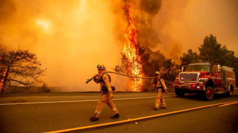 Firefighters try to stop a wildfire as wind drives embers across Highway 20 near Clearlake Oaks, Calif., on Sunday, July 1, 2018. (AP Photo/Noah Berger)