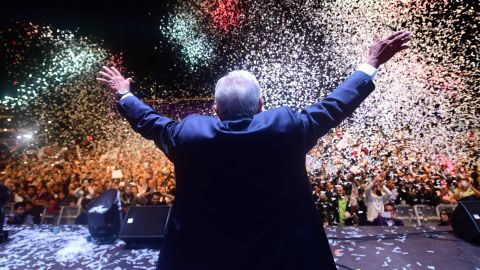 """TOPSHOT - Newly elected Mexico's President Andres Manuel Lopez Obrador (C), running for """"Juntos haremos historia"""" party, cheers his supporters at the Zocalo Square after winning general elections, in Mexico City, on July 1, 2018. (Photo by PEDRO PARDO / AFP)        (Photo credit should read PEDRO PARDO/AFP/Getty Images)"""