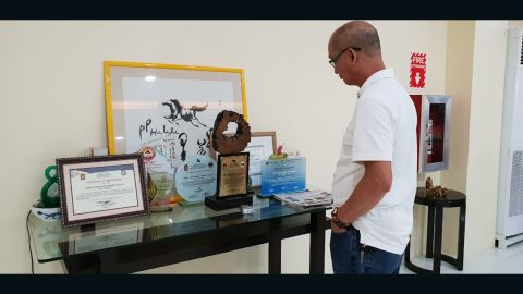 Mayor Halili's aide Carlos Mojares looks at his boss' awards and trophies. He says Halili was incredibly proud of his collection.