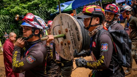 Rescuers carry equipments inside Tham Luang Nang Non cave.
