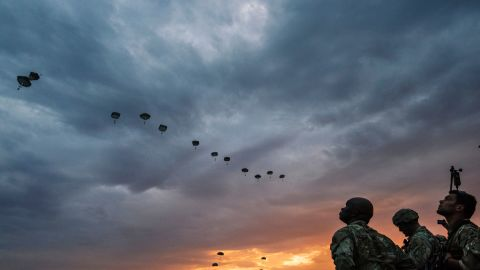 US Army soldiers look on while NATO paratroopers drop out of a US Air Force Hercules during the 'Swift Response 17' joint airborn military exercise at Bezmer airfield near the village of Bezmer on July 18, 2017.
