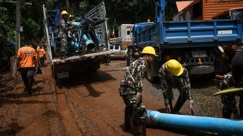 Technicians lift water pumps to the drilling site on July 1.