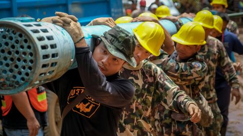 Rescue workers carry heavy water pumping equipment into Tham Luang Nang Non cave on July 1.