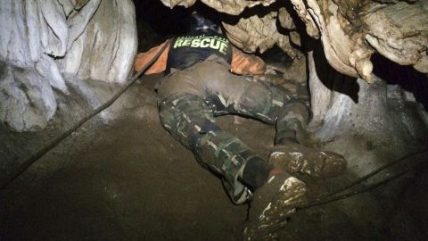 A rescuer looks for a cave entrance on June 27.