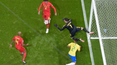 Belgian goalkeeper Thibaut Courtois leaps for a loose ball in the box.