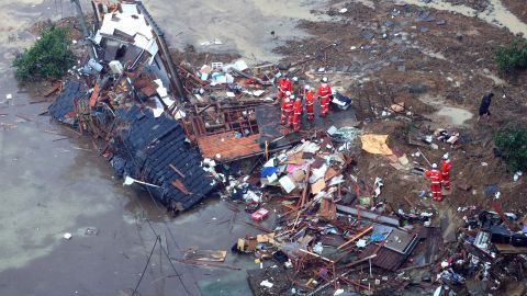 RESTRICTEDUWAJIMA, JAPAN - JULY 07:  (CHINA OUT, SOUTH KOREA OUT) In this aerial image, fire fighters checke a collapsed house which was washed away to a beach on July 7, 2018 in Uwajima, Ehime, Japan. 50 people are dead and at least 67 missing in heavy rains that have lashed western Japan since July 3, triggering landslides and flooding in wide areas.  (Photo by The Asahi Shimbun via Getty Images)