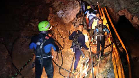 Thai military personnel walk into a cave during rescue operations.