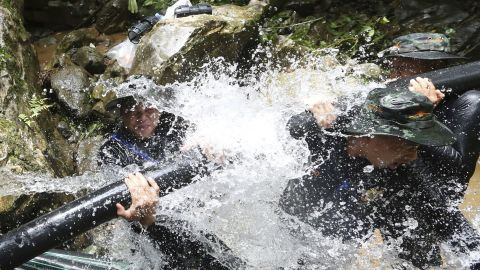 Thai soldiers work to connect pipes that help water from entering a cave.