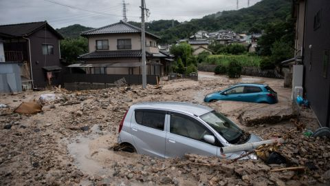 """TOPSHOT - A picture shows cars trapped in the mud after floods in Saka, Hiroshima prefecture on July 8, 2018. - Japan's Prime Minister Shinzo Abe warned on July 8 of a """"race against time"""" to rescue flood victims as authorities issued new alerts over record rains that have killed at least 48 people. (Photo by Martin BUREAU / AFP)        (Photo credit should read MARTIN BUREAU/AFP/Getty Images)"""