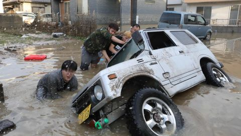 Residents try to upright a vehicle stuck in a flood hit area in Kurashiki, Okayama prefecture on July 9.