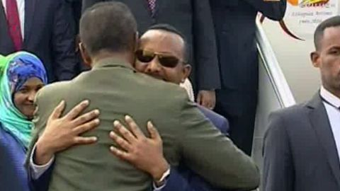 In this grab taken from video provided by ERITV, Ethiopia's Prime Minister Abiy Ahmed, background centre is welcomed by Eritrea's President Isaias Afwerki as he disembarks the plane, in Asmara, Eritrea, Sunday, July 8, 2018.