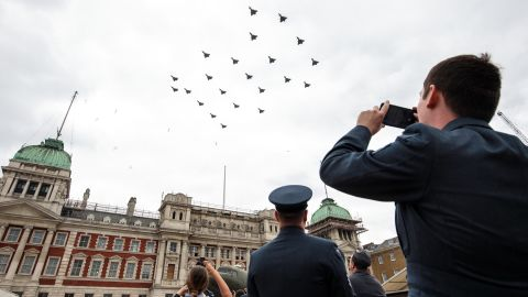 Members of the Royal Air Force watch Typhoon FGR4 aircraft fly over Horse Guards Parade.