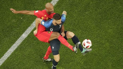 Giroud is challenged by Belgium defender Vincent Kompany.