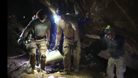 Rescuers carry one of the boys out of the cave.