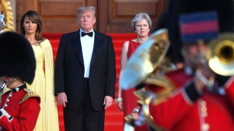Britain's Prime Minister Theresa May (R) US President Donald Trump (C) and his wife US First Lady Melania Trump (L) stand on steps in the Great Court watching and listening to the bands of the Scots, Irish and Welsh Guards perform a ceremonial welcome as they arrive for a black-tie dinner with business leaders at Blenheim Palace, west of London, on July 12, 2018, on the first day of President Trump's visit to the UK. - The four-day trip, which will include talks with Prime Minister Theresa May, tea with Queen Elizabeth II and a private weekend in Scotland, is set to be greeted by a leftist-organised mass protest in London on Friday. (Photo by Ben STANSALL / POOL / AFP)        (Photo credit should read BEN STANSALL/AFP/Getty Images)