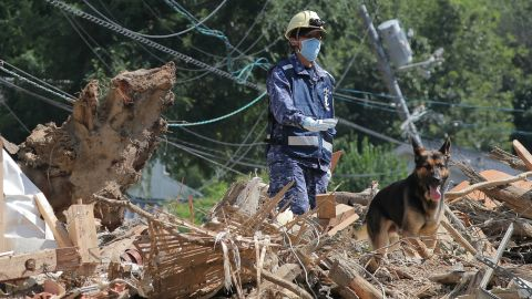A member of Japan's Maritime Self Defense Forces searches for missing persons at a flood damage site in Kure, Hiroshima prefecture on Thursday.