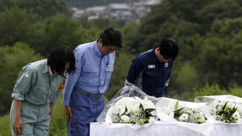 Prime Minister Shinzo Abe offer flowers at a hill he can see the submerged area on Wednesdayv in Kurashiki, Okayama, Japan.
