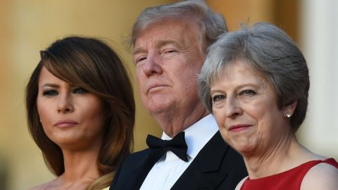 TOPSHOT - (L-R) US First Lady Melania Trump, US President Donald Trump and Britain's Prime Minister Theresa May stand on steps in the Great Court as the bands of the Scots, Irish and Welsh Guards perform a ceremonial welcome as they arrive for a black-tie dinner with business leaders at Blenheim Palace, west of London, on July 12, 2018, on the first day of President Trump's visit to the UK. - The four-day trip, which will include talks with Prime Minister Theresa May, tea with Queen Elizabeth II and a private weekend in Scotland, is set to be greeted by a leftist-organised mass protest in London on Friday. (Photo by Geoff PUGH / POOL / AFP)        (Photo credit should read GEOFF PUGH/AFP/Getty Images)