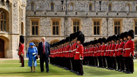 """US President Donald Trump is accompanied by Britain's Queen Elizabeth II as he inspects the Guard of Honour at Windsor Castle in Windsor, west of London, on July 13, 2018 on the second day of Trump's UK visit. - US President Donald Trump on Friday played down his extraordinary attack on Britain's plans for Brexit, praising Prime Minister Theresa May and insisting bilateral relations """"have never been stronger"""", even as tens of thousands protested in London against his visit. (Photo by Brendan Smialowski / AFP)        (Photo credit should read BRENDAN SMIALOWSKI/AFP/Getty Images)"""