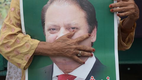 A supporter of ousted former Pakistani prime minister Nawaz Sharif holds his picture ahead of a rally led by his younger brother.