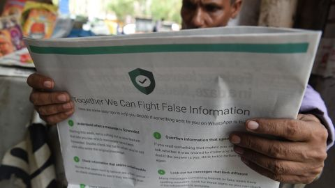 This photo illustration shows an Indian newspaper vendor reading a newspaper with a full back page advertisement from WhatsApp intended to counter fake information, in New Delhi on July 10, 2018.