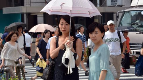 Pedestrians use their parasols to avoid strong sunlight in Tokyo on July 12.