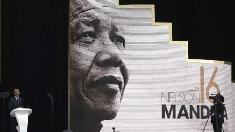 Obama speaking in front of an image of Nelson Mandela.