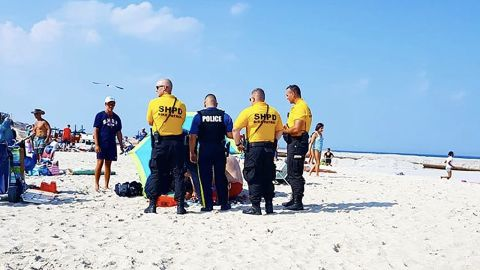 A tourist was basking on the beach when the stake of a flying umbrella went through her ankle, police said.